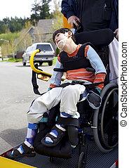 Disabled boy on school bus wheelchair lift