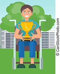 Disabled boy on wheelchair holding winner cup and smiling. Happy champion with incapacitation win goblet.