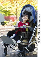 Disabled boy with cerebral palsy in medical stroller...