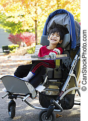 Disabled boy with cerebral palsy in medical stroller...
