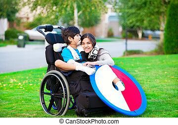 Disabled brother hugging older sister while sitting in wheelchair outdoors