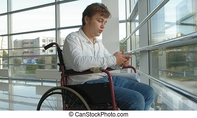 disabled businessman on a wheelchair at a window uses smartphone