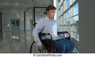 disabled businessman on a wheelchair at a window with a laptop