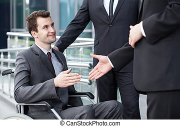 Disabled businessman shaking hand with business partners