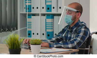 Handicapped businessman with visor and protection mask talking with colleague in financial company respecting social distance during global pandemic. Freelancer working in new normal business office.