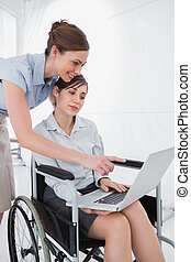 Disabled businesswoman looking at laptop with colleague