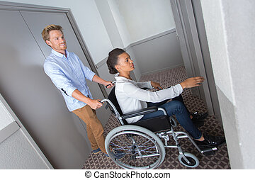 disabled businesswoman with her colleague pushing her in a lift