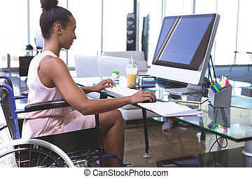 Disabled businesswoman working on computer at desk - Side ...