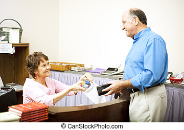 Disabled Clerk Serves Customer - Store clerk in a wheelchair...