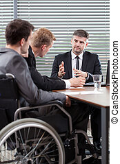 Disabled employee next to conference table, vertical