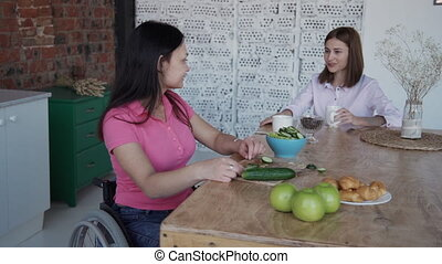 Woman in comfort wheelchair making salad and talking on...