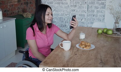 Young woman in wheelchair talking with friends using...
