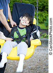 Disabled five year old boy in handicap swing