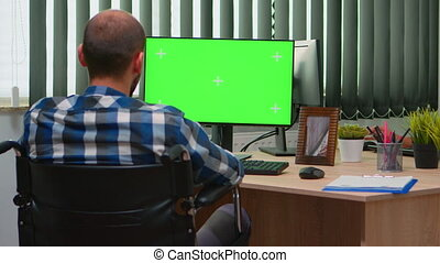 Handicapped disabled freelancer looking at pc with green screen talking with colleagues. Immobilized businessman in wheelchair using computer with chroma key, mockup, greenscreen for videomeeting.