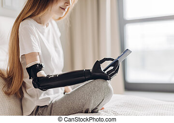 disabled girl holding her mobile phone with a robotic arm....