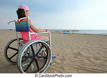 disabled girl sitting in a wheelchair look at the sea