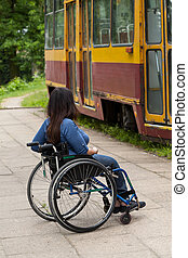 Disabled girl waiting for a tram