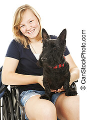 Portrait of a beautiful teen girl in a wheelchair holding her Scotty dog. White background.