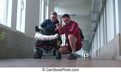 Disabled husband and wife talking in the hallway.