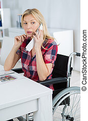Disabled lady sat at desk on telephone