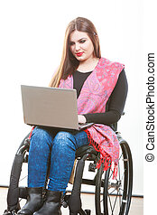 Disabled lady surfing on web. Young female on wheelchair...