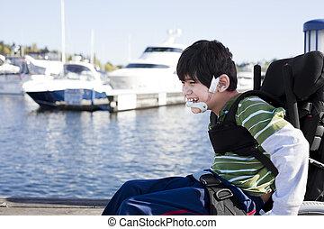 Disabled little boy in wheelchair