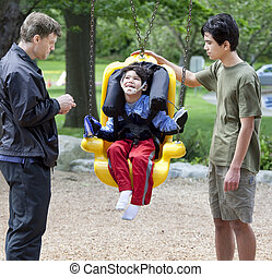 Disabled little boy swinging on special needs swing