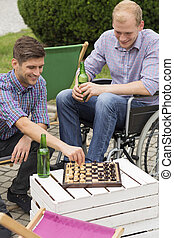 Disabled man and brother playing chess