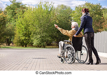 Disabled senior man and female caregiver outdoors