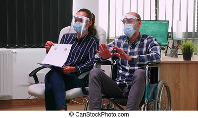 Businessman in wheelchair and woman partner with face masks having videomeeting in business office during global pandemic. Disabled freelancer working in financial company respecting social distance.