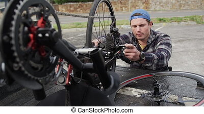 Front view of a Caucasian man in a wheelchair assembling parts of a recumbent bicycle in the boot of his car by the sea in slow motion