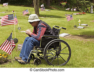 disabled man at the cemetery - disabled man in a wheelchair...