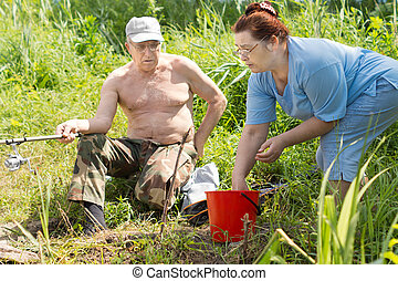 Disabled man being helped to fish by his wife - Disabled man...