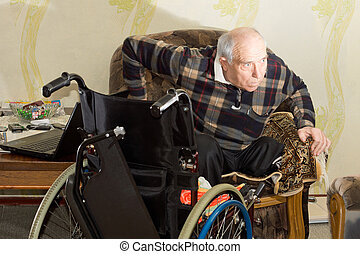 Disabled man changing from a chair to a wheelchair
