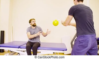 Disabled man doing hand exercises at the rehabilitation...
