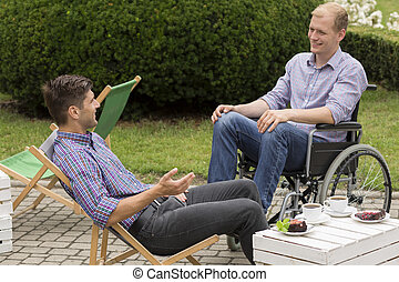 Disabled man drinking coffee with friend