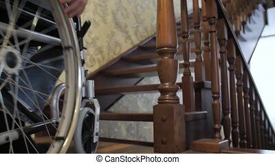 Handicapped man on a wheelchair drives up the stairs