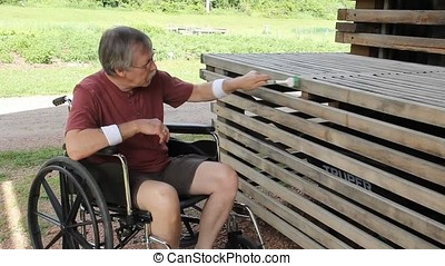 Disabled man in a wheelchair cleaning a garden bench...