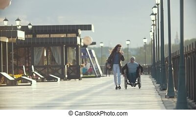 Disabled man in a wheelchair talking on the phone walking...