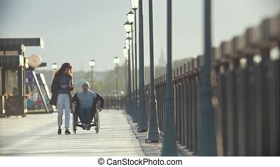 Disabled man in a wheelchair walking together her girlfriend...