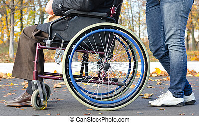 Disabled man in a wheelchair with a carer - Low angle close...