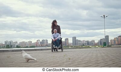 Disabled man in a wheelchair with young woman playing with a pigeon