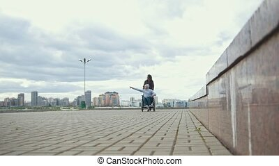 Disabled man in a wheelchair with young woman walking at the city street