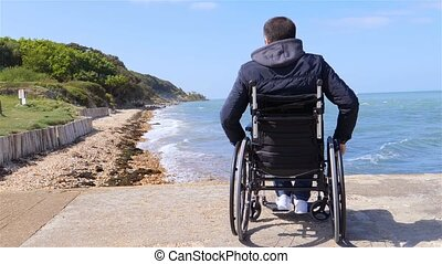 Disabled man in wheelchair at beach slow motion - Back of...