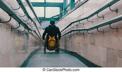 Disabled man in wheelchair carefully getting down the long ramp. Mid shot