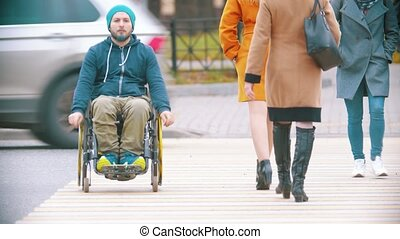 Disabled man in wheelchair crossing the road at the day time. Mid shot