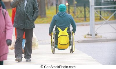 Disabled man in wheelchair crossing the road at the daylight. Mid shot