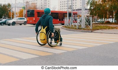 Disabled man in wheelchair crossing the road in the city. Mid shot