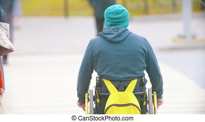 Disabled man in wheelchair crossing the road. Mid shot