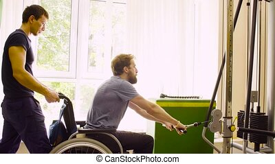 Disabled man in wheelchair doing hand exercises - Young...